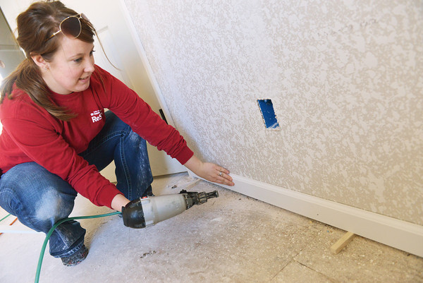 Globe/Roger Nomer<br /> Madison Hoffpauir, volunteer coordinator with Joplin Area Habitat for Humanity, nails down a baseboard at a house near 17th and Pennsylvania on Monday.