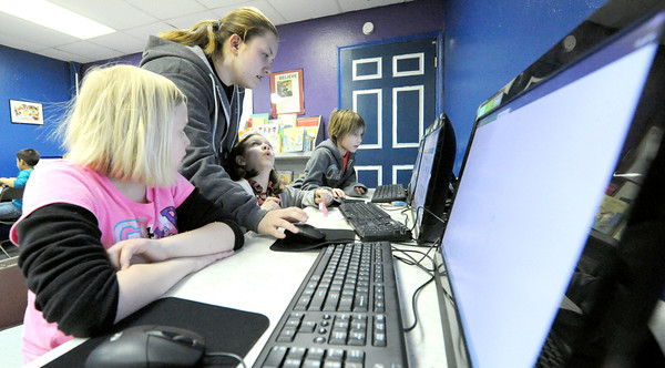 Reading coordinator Haley Mason helps kids log on to a program which allows them to read, write and even publish their own books at the Joplin Boys and Girls Club afterschool program on Friday. Pictured, left to right: Emaleigh Downey, 10, Mia Jasinski, 10 and Amricus Emmett, 9.<br /> Globe | Laurie Sisk