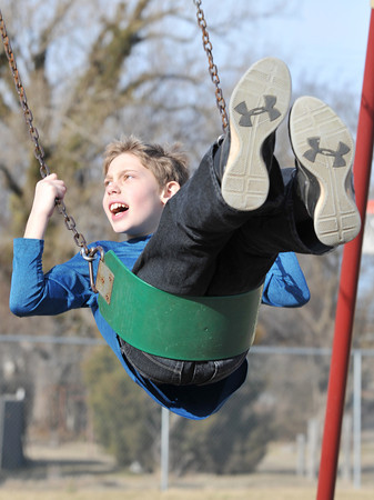 Eleven-year-old Corbin Boucher plays on the swings at the Joplin Boys and Girls Club afterschool program on Friday.<br /> Globe | Laurie Sisk