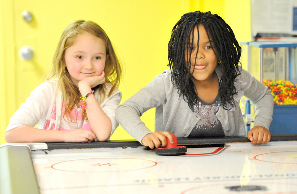 Seven-year-old Addison Wilcoxson, left and six-year-old Adyson Ratliff enjoy a game of air hockey at the Joplin Boys and Girls Club afterschool program on Friday.<br /> Globe | Laurie Sisk