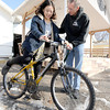 Don Smith helps EunJee Lee, South Korea, onto a loaner bicycle on Thursday at Campus Christians in Pittsburg. The organization has loaned about 250 bikes this year to international students at Pittsburg State University.<br /> Globe | Laurie Sisk