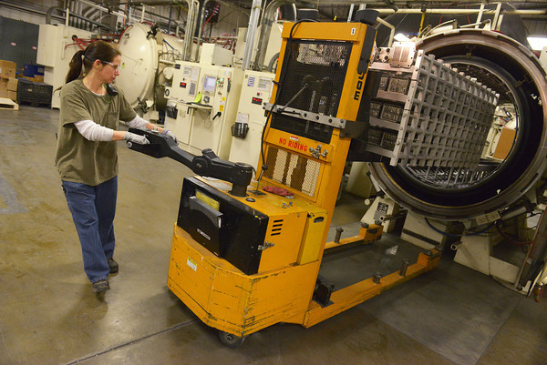 Globe/Roger Nomer<br /> Diane Anthon loads a vacuum braze furnace at Modine Manufacturing on Wednesday.