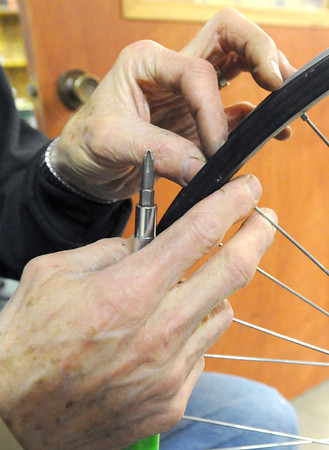 Don Smith replaces the spokes of a bike wheel at Campus Christians in Pittsburg. The organization has loaned about 250 bikes this year to international students at Pittsburg State University.<br /> Globe | Laurie Sisk