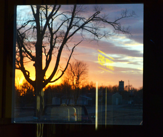 Globe/Roger Nomer<br /> The Country Fresh sign above the dessert case is reflected in the sunset through a window at Cowboy Bob's in Asbury on Feb. 15, 2014.