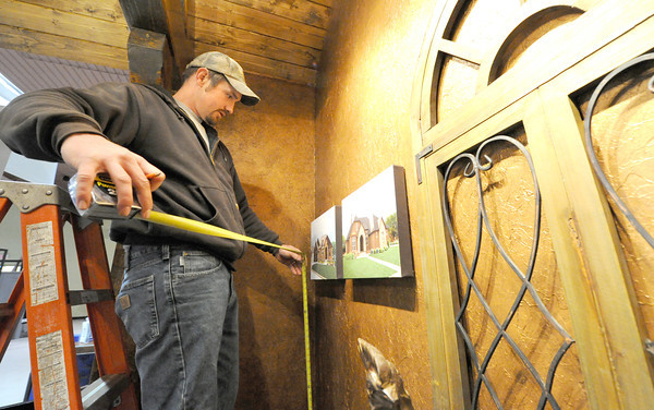 Caleb Turner, of Rose Construction, helps set up a display for the Home Builders Association home show, which opens Friday at the Holiday Inn Convention Center.<br /> Globe | Laurie Sisk