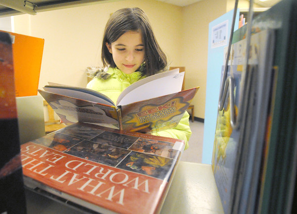 Machaira Wasson, 10, spends a snow day looking through stacks of books at the Joplin Public Library on Wednesday. wasson was looking for a book to help her plan a sushi party for her birthday.<br /> Globe | Laurie Sisk