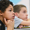 Globe/Roger Nomer<br /> During a presentation on Thursday at Pittsburg Middle School, Deonte Duncan, left, and Grant Oehme, sixth grade, listen to Manon Bol talk about his escape from a militia in Sudan.