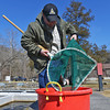 Globe/Roger Nomer<br /> Dustin Back, resource assistant, transfers trout to a bucket to prepare them for an assessment on Friday, Feb. 14, 2014.