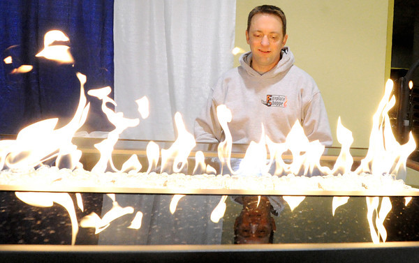 Victor Ferguson sets up a outdoor fire/chat table for The Fireplace shop in preparation for the Home Builders Association home show, which opens Friday at the Holiday Inn Convention Center.<br /> Globe | Laurie Sisk