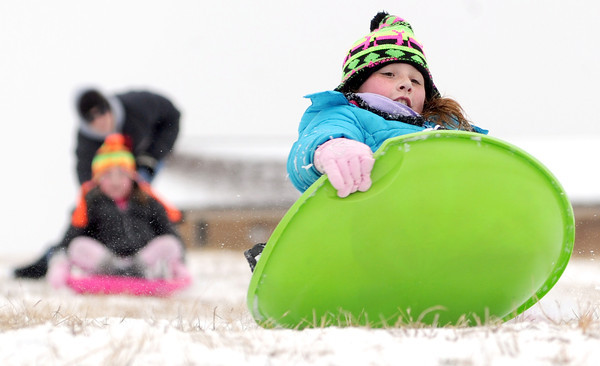 Konnar Davenport, 10, slides down a hill at McClelland Park as her mother, Kim Davenport, pushes her little sister, Klaire Davenport, 8, down the snowy slopes on Tuesday afternoon.<br /> Globe | Laurie Sisk