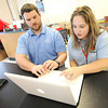 Webb City Junior High School seventh grader Lea Byrd helps woodshop teacher Drew Gollhofer how to use Twitter on Friday at the school. Byrd is one of 22 student e-leaders at the school.<br /> Globe | Laurie Sisk