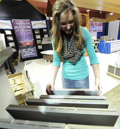 Sheridan Lake, of Signature Interior Expressions, organizes materials for their diplay on Thursday in preparation for the Home Builders Association home show, which opens Friday at the Holiday Inn Convention Center.<br /> Globe | Laurie Sisk