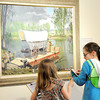 """Seven-year-old Chrysanna Harter. left and Jae Gubera, 11, take notes while examining a Roy Kerswill painting, """"A Kansas River Crosiing,"""" on Tuesday afternoon at the George A. Spiva Center for the Arts. The two are part of an afterschool program for children at Spiva called Creation Station.<br /> Globe 
