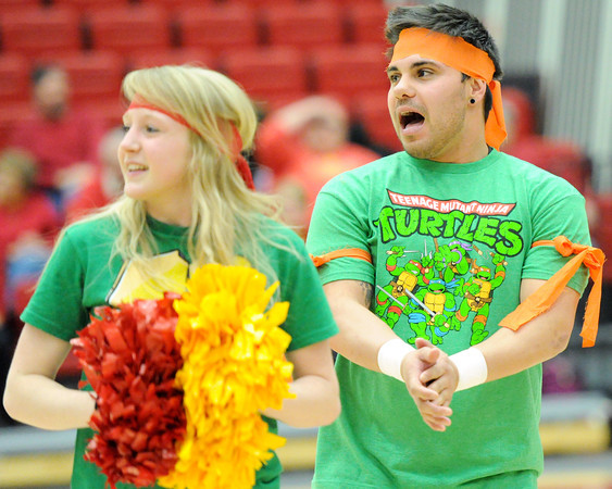 Pittsburg State yell leaders Hannah Pio, left and Adrian McElroy cheer for their team dressed in Teenage Mutant Ninja Turtle outfits. Yell leaders and fans have started coming to games dressed as their favorite superheroes as a way of getting the student body more involved in the basketball programs.<br /> Globe | Laurie Sisk