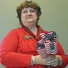 Globe/Roger Nomer<br /> Tami Kester, Neosho, hands out American flags before Monday's deployment ceremony at Pierce City High School. Kester's son is in the 276th.