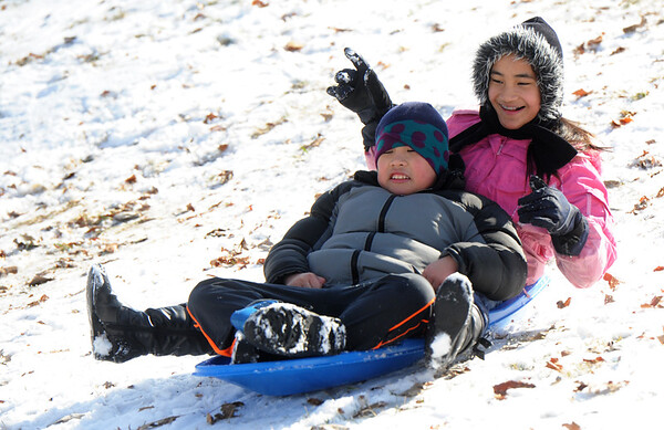 Jeevei Kionisala, left and his sister, Jem Kionisala, 10, enjoy a ride down a slope at Landreth Park on Tuesday afternoon.<br /> Globe | Laurie Sisk