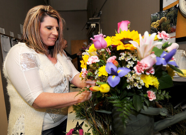 Floral designer Sheila Bush creates a large arrangement on Wednesday at Countryside in the City. Designers at the shop said designing floral arrangements is a combination of training and natural talent.<br /> Globe | Laurie Sisk