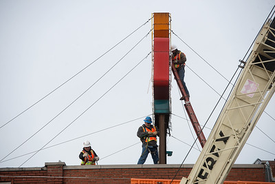 Workers prepare the Wilder's Restaurant sign for removal on Friday in Joplin. Globe | Roger Nomer