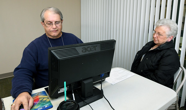 From the left: Second-year VITA volunteer Jeff Hughey assists Pat Meyer with her 2017 taxes on Thursday at Great Plains Credit Union.<br /> Globe | Laurie Sisk