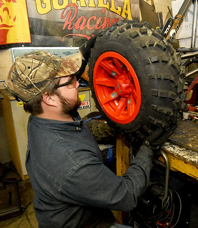 PSU Baja's Drew Harmon places one of the wheels on the club's car on Wednesday night at Pittsburg State. Members wil spend more than 2,500 hours getting their vehicle ready for competition.<br /> Globe | Laurie Sisk