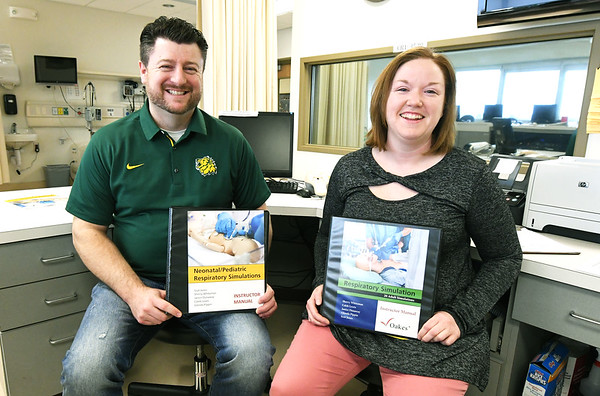From the left: Caleb Lewis and Sherry Whiteman hold textbooks they authored in collaboration with three additional faculty members for use by other institutions on uses for simulation mannequins.<br /> Globe | Laurie Sisk