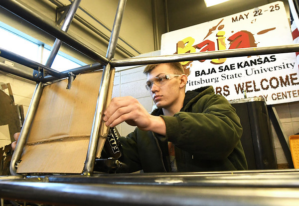 PSu Baja's Clay Nye uses cardboard to create a mock-up for a body panel on the club's vehicle on Wednesday night at PSU. Members wil spend more than 2,500 hours getting their vehicle ready for competition.<br /> Globe | Laurie Sisk