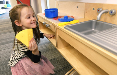 Five-year-old Anna Pennock, of Galena, exercises her culinary creativity while playing in the toy kitchen on Thursday at the Joplin Public Library. Globe   Laurie Sisk