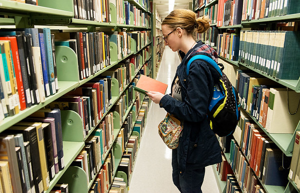 Michelle Borr, a Missouri Southern freshman from Bentonville, browses books at MSSU's Spiva Library on Thursday.<br /> Globe | Roger Nomer