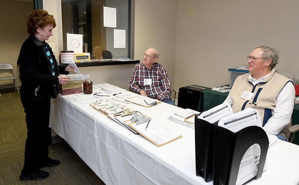 From the left: Sandy McMullen checks in with VITA volunteers George Kelly and Luke Moyer on Thursday at Great Plains Credit Union.<br /> Globe | Laurie Sisk