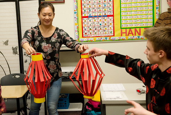 Fang Martin hands out Chinese lanterns to decorate her classroom at Thomas Jefferson Independent Day School on Friday.