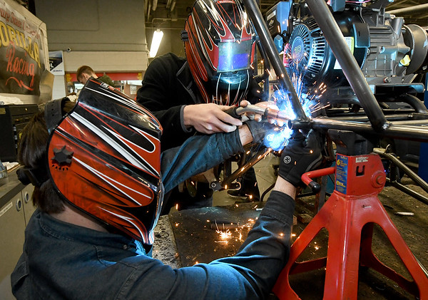 From the left: PSU Baja's Drew Harmon holds part of the rear suspension in place while fellow member Camden Mylott welds it in place on Wednesday night at PSU. Members wil spend more than 2,500 hours getting their vehicle ready for competition.<br /> Globe | Laurie Sisk