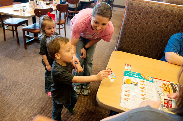 Easton Howard, 3, accompanied by sister Emma, 2, and mother Laurae, hands out an informational card about Children's Miracle Network to customers on Tuesday as part of the National Pancake Day event at IHOP. The restaurant served free pancakes as customers made donations to Children's Miracle Network. The charity has helped the Howard family since Easton and his twin Isaac were born at 26 weeks.<br /> Globe | Roger Nomer