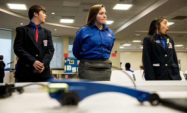 From left, Ethan Myers, Commerce High freshman, Stormie Lovan, sophomore, and Gaby Medina, Commerce Middle School eighth grader, watch a CO2 car race at the Regional TSA Conference on Friday at Missouri Southern.<br /> Globe | Roger Nomer