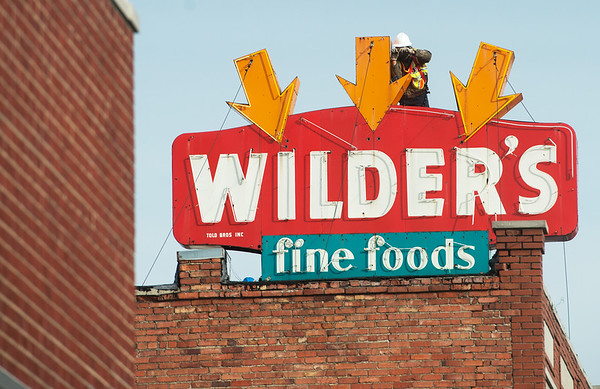A worker prepares the Wilder's Restaurant sign for removal on Friday in Joplin.<br /> Globe | Roger Nomer