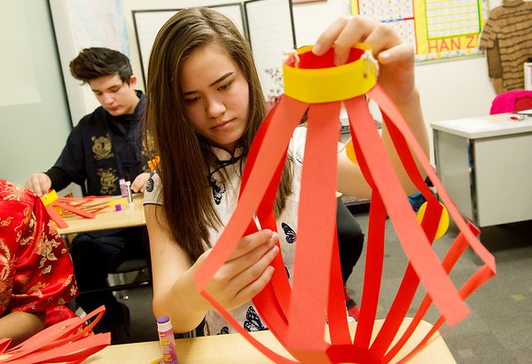 Jade Eschenbrenner, Thomas Jefferson Independent Day School sophomore, glues a decoration with a wish for the Chinese New Year to a lantern during class on Friday.<br /> Globe | Roger Nomer