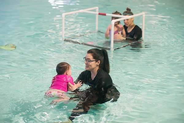 Brittany Harris, of SuperStar Aquatics, helps Stella White, 10 months, with swimming skills on Wednesday at the Joplin YMCA pool.<br /> Globe | Roger Nomer