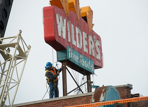 A worker cuts the support post on the Wilder's Restaurant sign on Friday.<br /> Globe | Roger Nomer