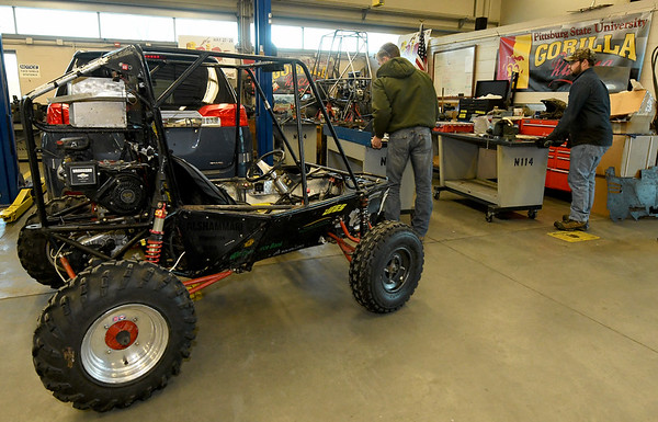 PSU Baja members work on this year's buggy as last year's sits in the foreground PSu Baja senior Michael Holland works on the front suspension he designed for the club's buggy on Wednesday night at PSU. <br /> Globe | Laurie Sisk