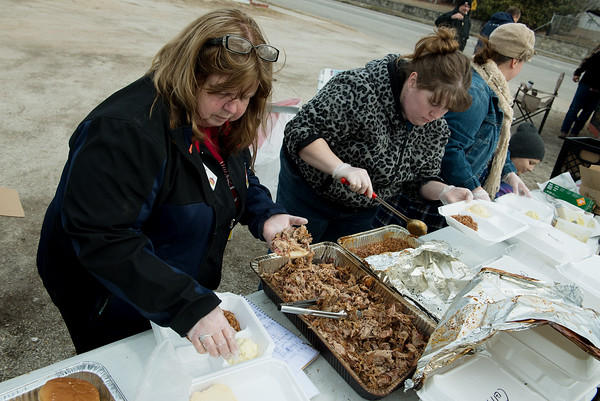 Pam Lawrence, Casey's General Store manager, left, and Lisa Coleman, cashier, prepare pulled pork sandwiches during a Casey's fundraiser for the Children's Miracle Network on Friday in Galena.<br /> Globe | Roger Nomer