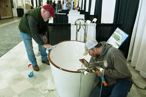 Jeff Owen, sales manager for Joplin Supply Company, left, and Isaiah Johnson, warehouse manager, prepare their booth on Thursday at the Home Builders Association Home Show at North Point Shopping Center. <br /> Globe | Roger Nomer