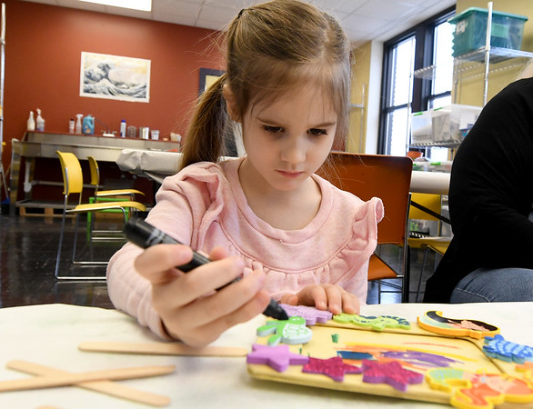 Four-year-old Natalie Isenberger is a study in concentration as she decorates a picture frame during Shutterbugs last Saturday at the Spiva Center for the Arts.<br /> Globe | Laurie Sisk