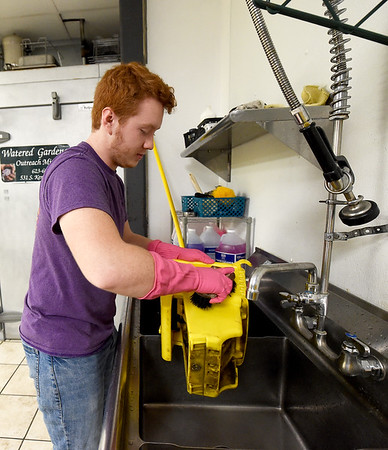 Carl Junction High School Spanish National Honor Society student Christian Byron, 18, helps clean the kitchen at Watered Gardens on Saturday. About 25 students from the society volunteered their time on Saturday for a variety of projects at the shelter.<br /> Globe | Laurie SIsk