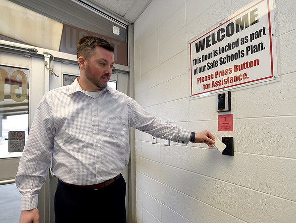 Carl Junction High School Assistant Principal Kyle Williams uses the card swipe system for entry on Tuesday at CJHS.<br /> Globe | Laurie Sisk