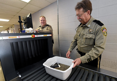 From the left: Jasper County Deputies James Marler and Gary Mason scans items on Friday at the entrance of the Jasper County Courts Building. Globe | Laurie Sisk