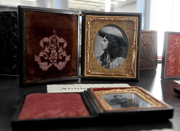 A photograph of infamous cowgirl Annie Oakley sits above a photo of Calamity Jane as part of an Allen Shirley collection of about 50 infamous public figures captured in three different types of photographic processes now on display at the Joplin Public Library.<br /> Globe | Laurie Sisk