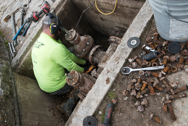 Charles Brewer, with Martin General Contracting, replaces valves and fittings, many from the 1930's, at the Roaring River State Park hatchery on Thursday.<br /> Globe | Roger Nomer