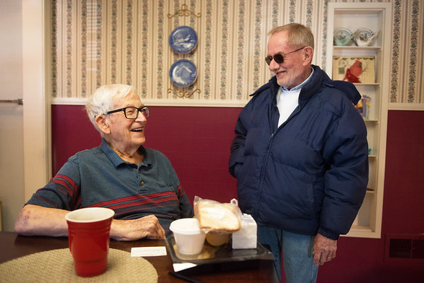Bill Taber, left, talks with Mike Howard after being delivered lunch from Meals on Wheels on Friday.<br /> Globe | Roger Nomer