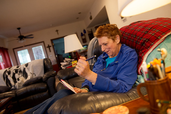 Debi Sierra listens to KRPS while working on a word search in her Joplin home on Wednesday.<br /> Globe | Roger Nomer