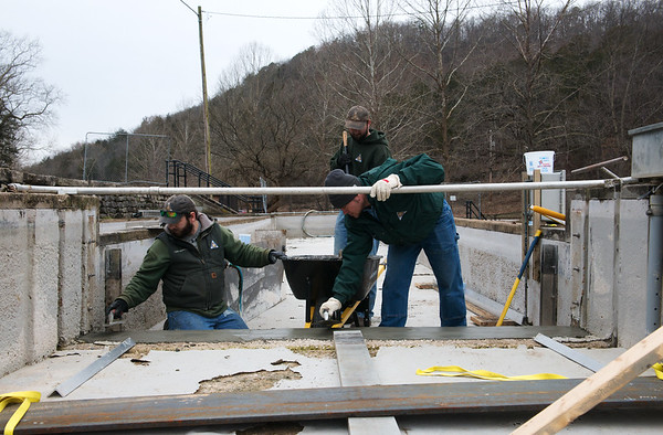 (from left) Caleb Beuterbaugh, Justin Ballard and Brad Farwell work on a raceway at the Roaring River State Park hatchery on Thursday.<br /> Globe   Roger Nomer