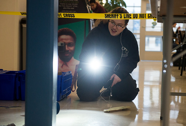 Stormy Tramell, a Seneca High junior, uses a flashlight to explore a mock crime scene during Engineering Day at Crowder College on Wednesday.<br /> Globe   Roger Nomer